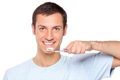 Hombre joven que aplica sus dientes con brocha Imagen de archivo libre de regalías