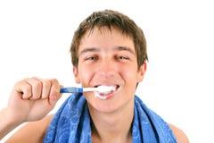 Hombre joven que aplica sus dientes con brocha Fotografía de archivo