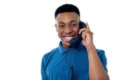 Hombre joven que asiste a llamada de teléfono imagenes de archivo
