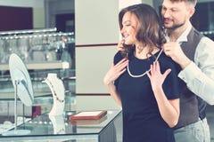 Hombre joven que ayuda a su novia con el collar apropiado en el je fotos de archivo libres de regalías