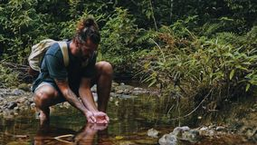 hombre joven que bebe del río cristalino en el medio de la selva tropical tropical de la selva foto de archivo