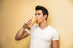 Hombre joven que bebe el vidrio grande de fruta sana Fotos de archivo libres de regalías