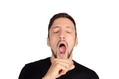 Hombre joven que bosteza foto de archivo
