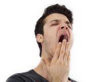 Hombre joven que bosteza en aislado Fotografía de archivo libre de regalías