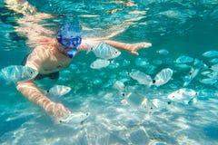 Hombre joven que bucea en arrecife de coral subacuático en la isla tropical Foto de archivo