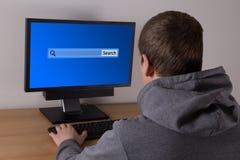Hombre joven que busca algo en Internet Imagenes de archivo
