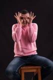 Hombre joven que busca algo, haciendo los prismáticos con sus manos Imagen de archivo