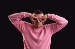 Hombre joven que busca algo, haciendo los prismáticos con sus manos Imagen de archivo libre de regalías