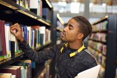 Hombre joven que busca los libros en la biblioteca pública imagen de archivo