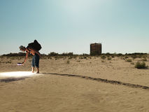 Hombre joven que busca a través de la arena con la luz Imágenes de archivo libres de regalías