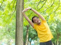 Hombre joven que calienta en parque Foto de archivo