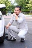 Hombre joven que cambia el neumático pinchado Imágenes de archivo libres de regalías