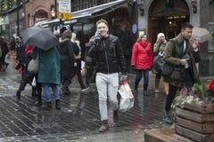 Hombre joven que camina abajo de la calle, hablando en el teléfono en la lluvia Fotografía de archivo libre de regalías