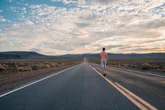Hombre joven que camina abajo del camino sin fin Imagen de archivo libre de regalías