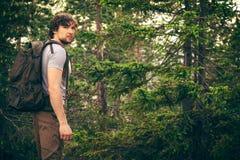 Hombre joven que camina en bosque con la mochila Foto de archivo libre de regalías