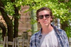 Hombre joven que camina en campus de la universidad con las gafas de sol Fotografía de archivo