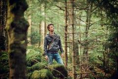 Hombre joven que camina en el bosque Foto de archivo libre de regalías