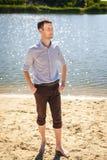 Hombre joven que camina en el río del coste Imagen de archivo libre de regalías