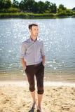 Hombre joven que camina en el río del coste Foto de archivo libre de regalías