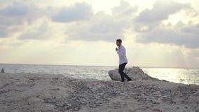 Hombre joven que camina en la playa y que goza sorprendiendo la vista de la playa chipre Paphos almacen de video