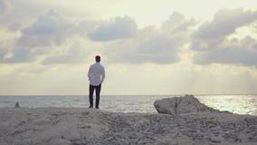 Hombre joven que camina en la playa y que goza sorprendiendo la vista de la playa y del tiempo hermoso chipre Paphos almacen de metraje de vídeo