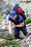 Hombre joven que camina en rastro de montaña difícil con el cable de la ejecución Imágenes de archivo libres de regalías
