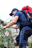 Hombre joven que camina en rastro de montaña difícil con el cable de la ejecución Foto de archivo libre de regalías