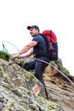 Hombre joven que camina en rastro de montaña difícil con el cable de la ejecución Fotografía de archivo libre de regalías