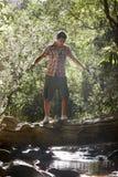 Hombre joven que camina en registro sobre corriente Fotografía de archivo