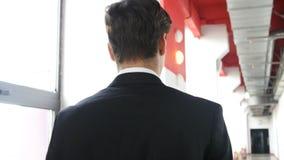 Hombre joven que camina en traje en el pasillo de la oficina, visión trasera Imágenes de archivo libres de regalías
