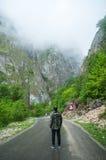 Hombre joven que camina en un camino de las montañas Foto de archivo libre de regalías