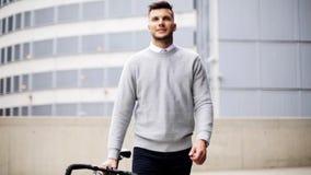 Hombre joven que camina a lo largo de la calle de la ciudad con la bicicleta