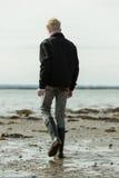 Hombre joven que camina solamente en la playa Fotografía de archivo libre de regalías