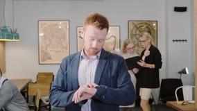 Hombre joven que camina a través de la oficina y que usa el reloj elegante app El hombre de negocios toca la pantalla y la sonris metrajes