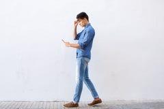 Hombre joven que camina y que lee el mensaje de texto en el teléfono celular Imagen de archivo