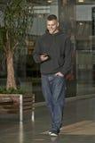Hombre joven que camina y que manda un SMS Imagen de archivo libre de regalías