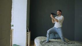Hombre joven que canta al secador de pelo y al rocknroll de baile en cama en dormitorio almacen de metraje de vídeo