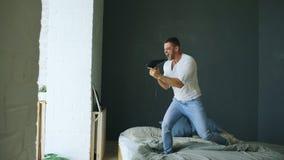 Hombre joven que canta al secador de pelo y al rocknroll de baile en cama en dormitorio imágenes de archivo libres de regalías
