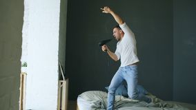 Hombre joven que canta al secador de pelo y al rocknroll de baile en cama en dormitorio fotografía de archivo
