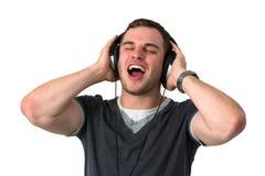 Hombre joven que canta con los auriculares en la pista Fotografía de archivo libre de regalías
