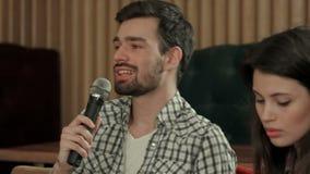 Hombre joven que canta la canción preferida en Karaoke metrajes