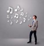 Hombre joven que canta y que escucha la música Foto de archivo libre de regalías