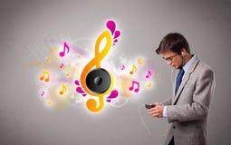 Hombre joven que canta y que escucha la música con las notas musicales Imagen de archivo libre de regalías