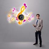 Hombre joven que canta y que escucha la música con las notas musicales Imágenes de archivo libres de regalías