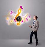Hombre joven que canta y que escucha la música con las notas musicales Fotografía de archivo libre de regalías