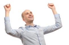 Hombre joven que celebra éxito con la mano levantada Foto de archivo