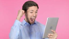 Hombre joven que celebra éxito en la tableta, fondo rosado almacen de video