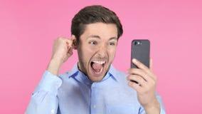 Hombre joven que celebra éxito mientras que usando Smartphone en fondo rosado almacen de metraje de vídeo