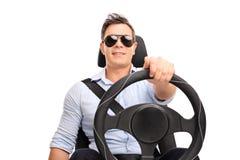 Hombre joven que celebra una conducción del volante imagen de archivo