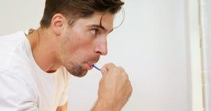 Hombre joven que cepilla sus dientes con el cepillo de dientes en el cuarto de baño 4K 4k almacen de video
